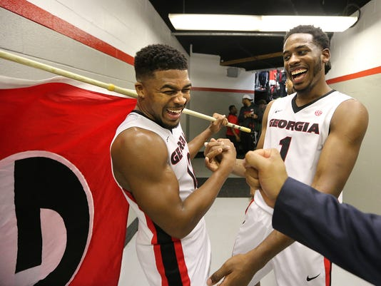 Georgia guard Kenny Gaines, left, and Forward Yante Maten continue the celebration off the court as they carry the Georgia flag out of the tunnel to the locker room after beating state rival Georgia Tech 75-61 in an NCAA college basketball game on Saturday, Dec. 19, 2015, in Athens.  (Curtis Compton/Atlanta Journal-Constitution via AP)  MARIETTA DAILY OUT; GWINNETT DAILY POST OUT; LOCAL TELEVISION OUT; WXIA-TV OUT; WGCL-TV OUT; MANDATORY CREDIT