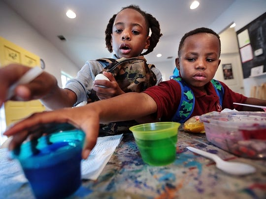 Materio Dorsey (left) and Marion Hawkins color Easter eggs for the first time at Purple House which is part of the Carpenter Art Garden Tuesday after school. The house and garden host tutoring and small group art lessons for neighborhood kids in the Binghampton area.