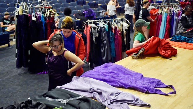 William Penn junior Melissa Rosario tries on a prom dress with help from senior Pedro Ocasio on Thursday in William Penn's auditorium. York Suburban sophomore Elise Atkinson collaborated with William Penn principal secretary Yenitza Lindsay to collect about prom dresses from community members and stores to give to William Penn and West York students. Their efforts yielded about 700 donated dresses - too many to fit on the racks for the first giveaway - resulting in additional giveaways at future dates.