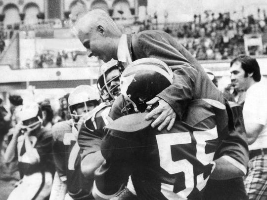 Brick players carry coach Warren Wolf off field after 21-20 triumph over Camden that gave Green Dragons the 1974 NJSIAA Group IV South Jersey championship.