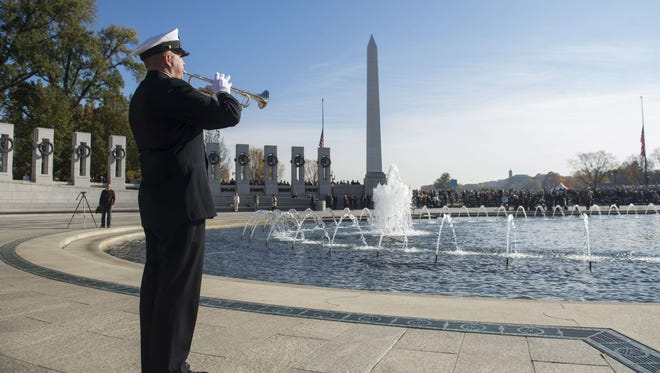 A US Navy Band bugler plays taps during a Veterans Day event at the World War II Memorial on the National Mall in Washington, DC.