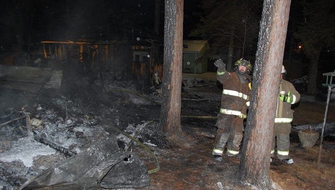 Firefighters on the scene of a fatal fire in the Clark County town of Dewhurst Friday morning.