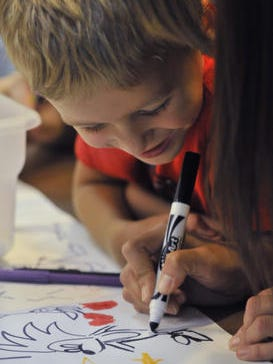 Mason Hovis, 6, watches as a cartoon character is drawn while volunteers with Martina McBride's Team Martina, assist with an art project while at Mary Ellen's Hearth, on Thursday July 17, 2014. Hovis lives at the homeless shelter with his mother.