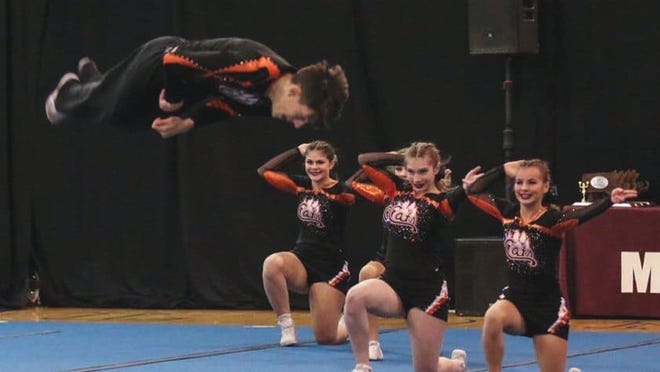 Gardner High senior Christopher Supple performs a jump while competing with the Wildcats cheer team this past season.