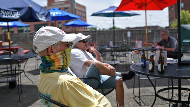 Patrons enjoy a drink and some food at Ralph's Tavern's outdoor dining area on Shrewsbury Street in Worcester Monday.