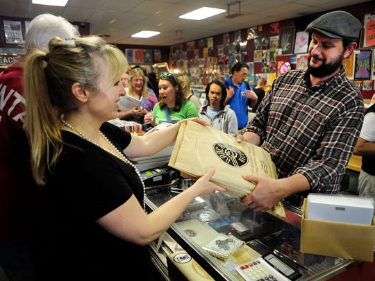 Sean Fallin, of Keizer, picks up his purchase from Lori Close, co-owner of Ranch Records, on Saturday, April 18, at the Salem store.