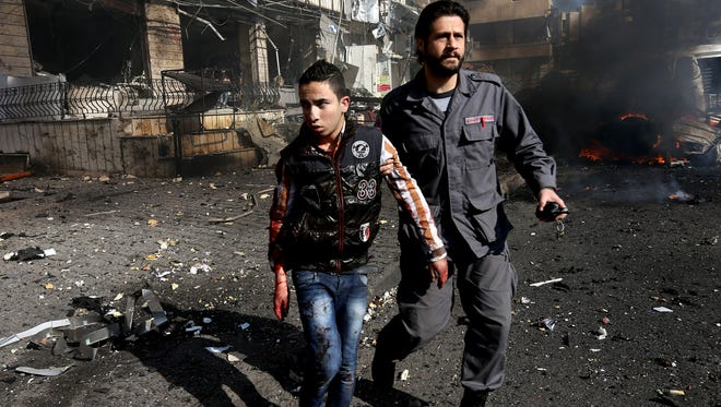 A Lebanese civil defense worker, right, helps a wounded man at the site of an explosion, near the Kuwaiti Embassy and Iran's cultural center, in a Beirut suburb on Feb. 19.