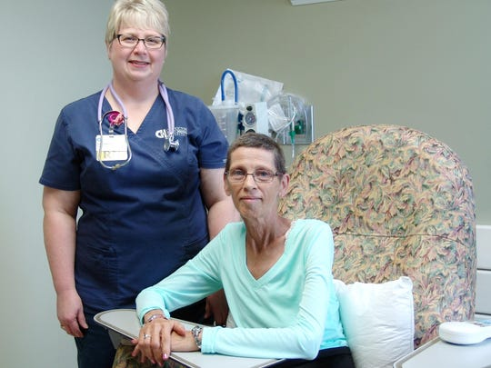 Shirley Foster, seated, and her oncology nurse, Susan Fitch, pose for a photo in a treatment room at Coshocton Hospital. Foster endured a mastectomy, chemotherapy and radiation, and the message she shares with others is to stay positive.
