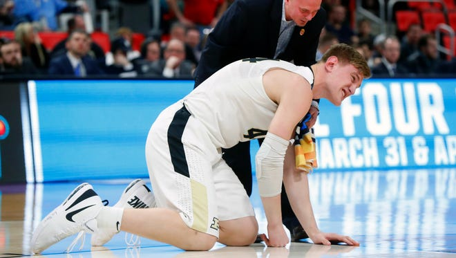 Purdue center Isaac Haas reacts to landing on the floor as a trainer attends to him against Cal State Fullerton during the second half of an NCAA men's college basketball tournament first-round game in Detroit, Friday, March 16, 2018.