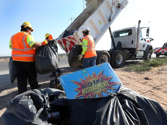 Crews from the Texas Department of Transportation pick up trash left by people who celebrated the 2017 Fourth of July along East Montana Avenue in the Montana Vista area.