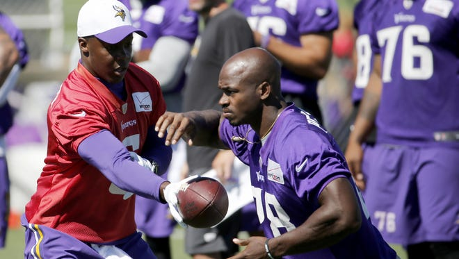 Minnesota Vikings quarterback Teddy Bridgewater hands the ball off to running back Adrian Peterson during Wednesday's practice at an NFL training camp on the campus of Minnesota State-Mankato in Mankato.