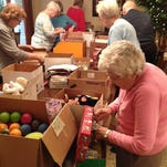 Vintage Hills at Prairie Trail residents and family members pack boxes for Operation Christmas Child. From left: Betty Spooner, Gwen Boulter, Joan Reich, Russell Tomlinson, Marjorie Mitchell and Laura Foster