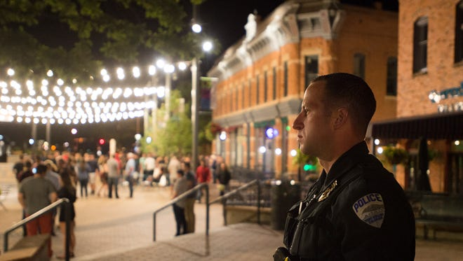 Officer Mike Harres keeps an eye on people leaving the bars and night clubs in Old Town Square Saturday, August 27, 2016.