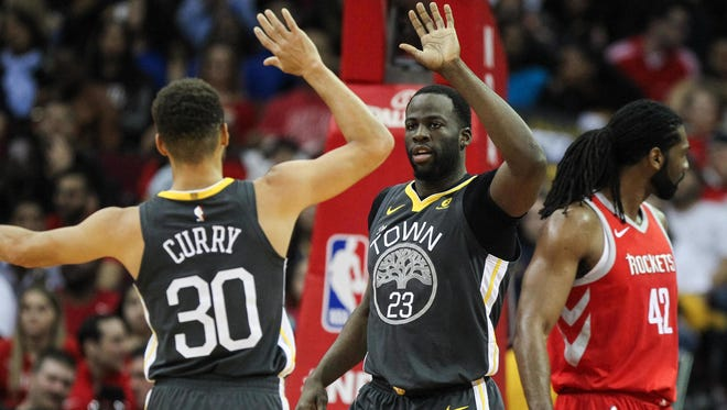 Golden State Warriors forward Draymond Green (23) celebrates with guard Stephen Curry (30) after a play during the game against the Houston Rockets at Toyota Center.