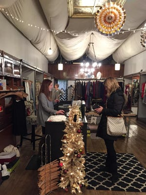 Lori Troutwine, left, serves a customer at Luxe Lizzies, during Small Business Saturday.