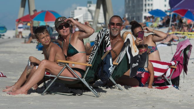 Kim Renninger, left center, and the rest of her family, grandson, Trapper Bechdel, left, husband, Rory, and daughter, Elizabeth Bechdel, right,  scans the skies for the Blue Angels during the Breakfast with the Blues event at Pensacola Beach Wednesday morning July 5, 2017.