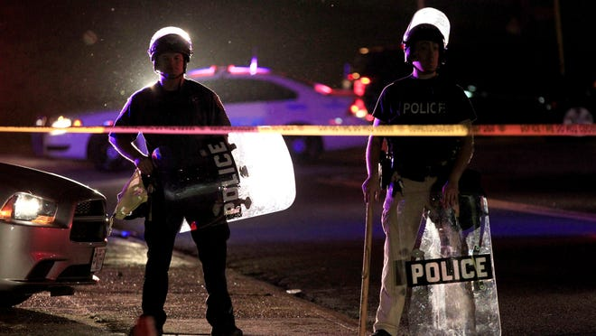 Police wearing riot gear stand at a post as they wait for a crowd to disperse Monday, Aug. 11, 2014, in Ferguson, Mo.