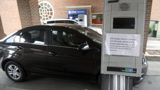Customers use the drive-thru teller machine and ATM as signs posted at PNC Bank advise the bank is collecting change due to the national coin shortage.