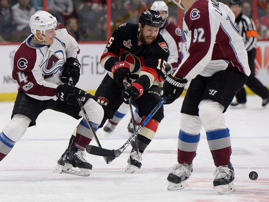 Ottawa Senators' Zack Smith (15) tries to control the puck against Colorado Avalanche's Tyson Barrie (4) during the first period of an NHL hockey game Thursday, March 2, 2017, in Ottawa, Ontario. (Justin Tang/The Canadian Press via AP)