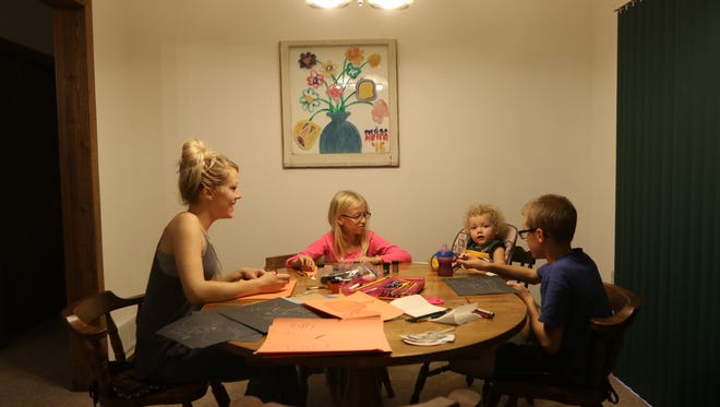 From left: Karly Tellekson laughs while making Halloween drawings with her children Keira; 10, Jordan; 11 and Quinn; 11 months, at the Tellekson residence in Wisconsin Rapids, Wisconsin. Karly Tellekson was bullied as a child, and was cautious in talking to adult figures, even blamed herself for it. Now, she learns from her own experiences when talking to her children.