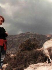 Mary watches as a goat ambles through Greece's mountainous