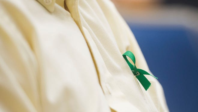 University of Tennessee student John Black wears a green ribbon for mental health awareness at a forum hosted by the Student Political Alliance on mental health on campus and suicide prevention, in the Walters Life Sciences building Tuesday, Oct. 10, 2017.