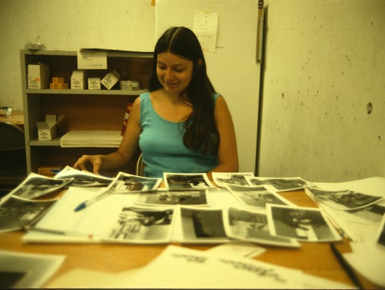 Peggy Roske, CSB/SJU archivist, is shown sorting photos