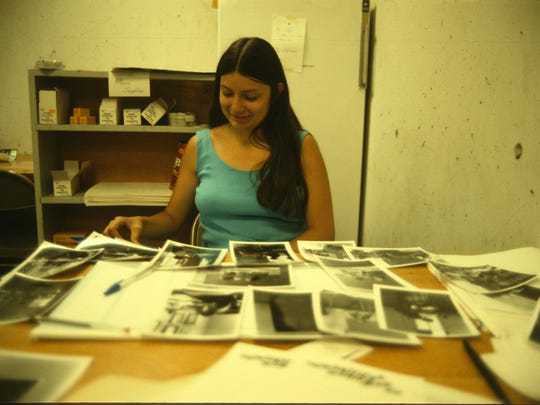 Peggy Roske, CSB/SJU archivist, is shown sorting photos for yearbooks earlier in her career.