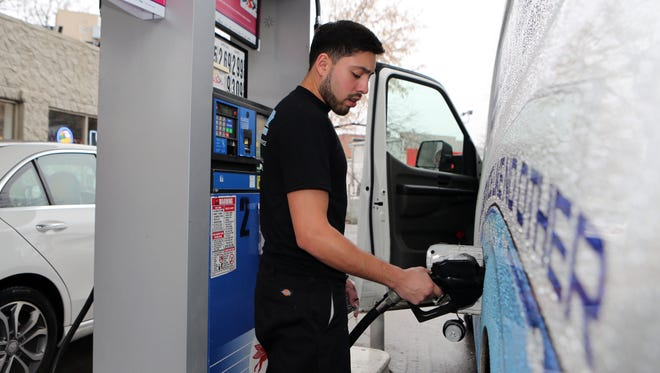 Brian Lozada, a plumber with Drain Saver, a sewer and drain service in White Plains, is dressed in a t-shirt as he fills the company truck with fuel at the White Plains Mobil on Mamaroneck Avenue.