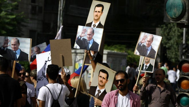 Protesters hold photos of Syrian President Bashar Assad and Russian President Vladimir Putin in Damascus on Oct. 13, 2015.