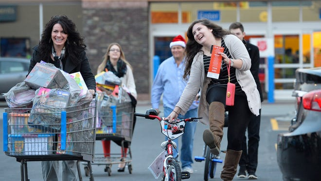Nicole Tatusko, left, and Kelly Hayes, right, help lead Frank Duffy to his van with baskets of toys and new bicycles during a toy drive that initially totaled 275 toys donated by clients and employees of his real estate firm, before Duffy matched the contributions and even increased it by 69 toys during a major shopping spree at a local Wal-Mart store on Friday, Dec. 19, 2014, in Alpharetta, Ga.