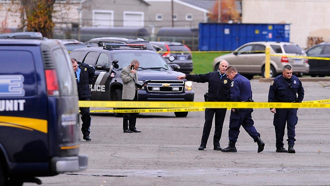 Lansing Police and investigators on the scene of a murder-suicide shooting in the parking lot behind the McLaren Greater Lansing Pennsylvania campus  in  Lansing  Monday morning    10/21/2014 .
