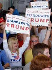 Supporters of Donald Trump wave signs after a campaign