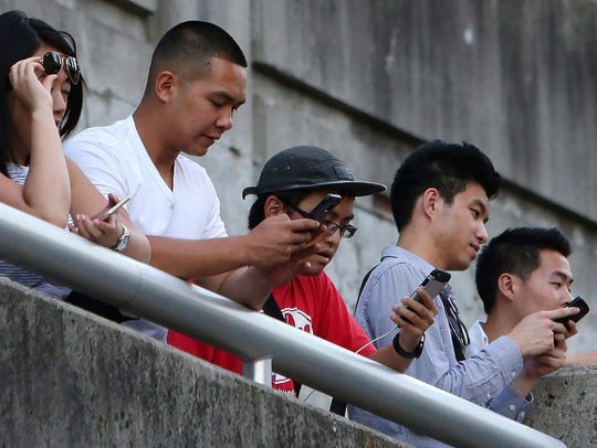 People use their phones in Toronto, Monday, July 18,