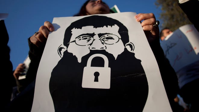 In this Tuesday, Feb. 21, 2012 , file photo, a Palestinian woman holds a poster with a drawing depicting Islamic Jihad member Khader Adnan with a locked mouth, who has been on hunger strike for two months, during a demonstration in Jerusalem.