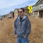 This March 21, 2014, photo shows Chris Talbott standing with a pile of tumbleweed in front of his home in Colorado Springs, Colo. Parts of Colorado are being overrun with tumbleweeds because of the drought affecting much of the western U.S.