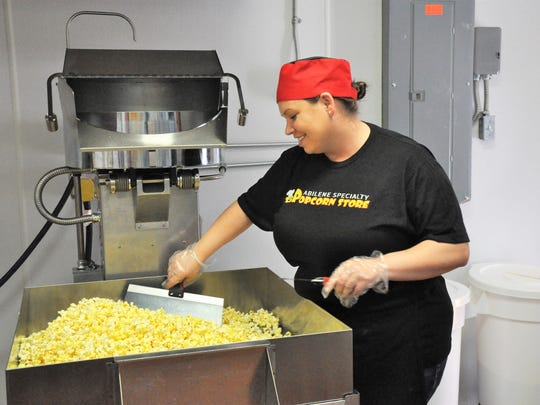 Abilene Specialty Popcorn Store chef Desiree Medlin uses paddles to sift through a fresh batch of popcorn on a screened table to remove any unpopped kernels on Wednesday.