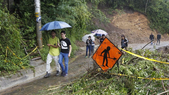 People walk pass by a debris filled road at the Llano area in Alajuelita, south San Jose, Costa Rica, Oct. 5, 2017.