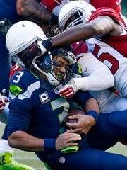 Arizona outside linebackers Chandler Jones (55) and Markus Golden sack Seattle's Russell Wilson in the first quarter.