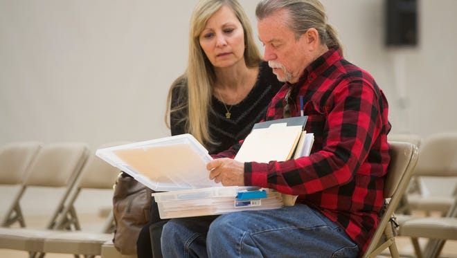 Craig and Faye Gibbs look over their paper work before the start of a public meeting hosted by the Tennessee Department of Commerce for Gatlinburg wildfire victims and their respective insurance agencies at the Rocky Top Sports World athletic complex on Thursday, Feb. 16, 2017. The Gibbs lived at Greystone Heights Road and lost everything in the fire. They are still in discussions with their insurance agency regarding compensation.