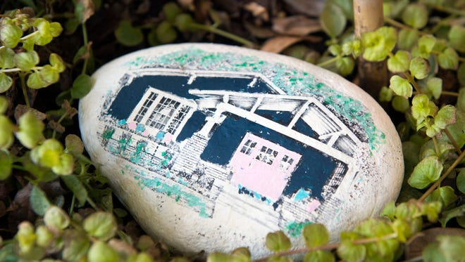 This painted rock, placed inside a planter next to the front door, depicts the renovated home.