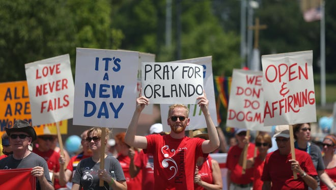 A man carries a sign responding to the shooting Orlando during the Capital City Pride Festival parade on Sunday, June 12, 2016, in Des Moines.