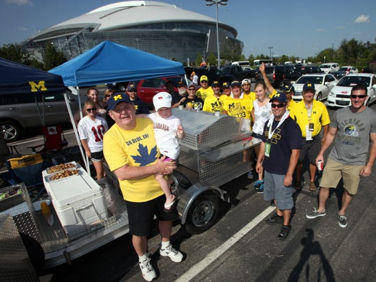 Michigan fans from the Windsor area pose at the tailgating party outside Cowboys Stadium in 2012.