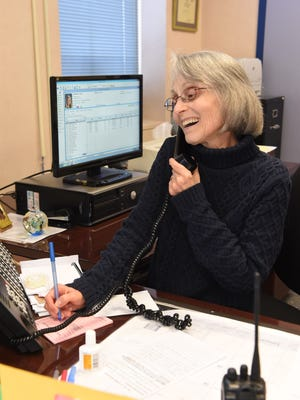 Madeline Paonessa, 69, secretary at Our Lady of Lourdes High School in the Town of Poughkeepsie, takes a call in the school's main office.