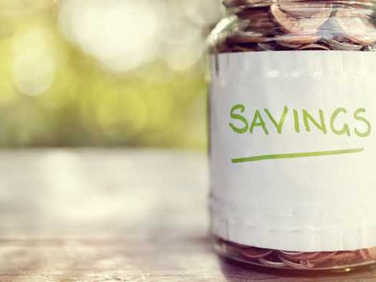 """A jar labeled """"savings"""" filled with coins"""