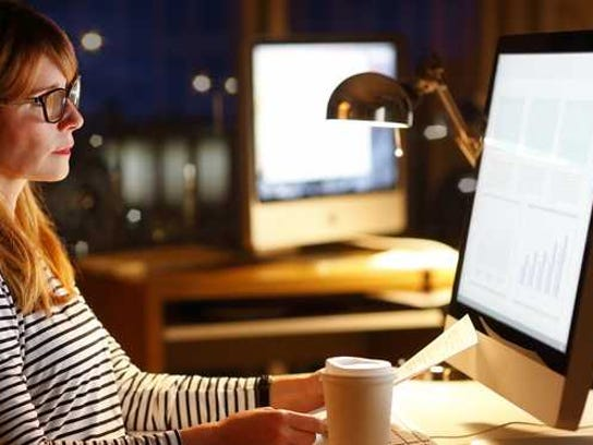 woman sitting in front of computer in office late at night