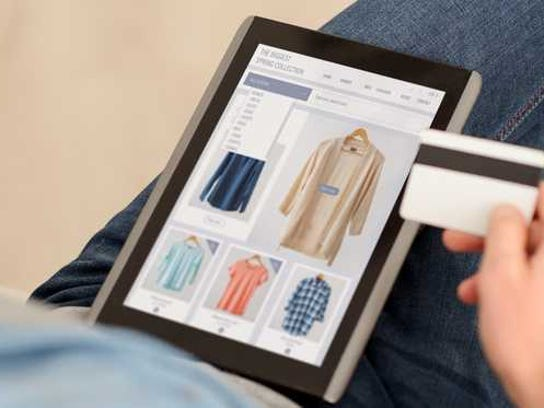 Person shopping online on a tablet holding a credit card.