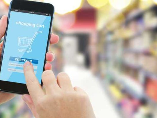 Hands use a mobile phone in a grocery store.