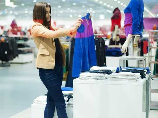 A female shopping for clothes off a display.