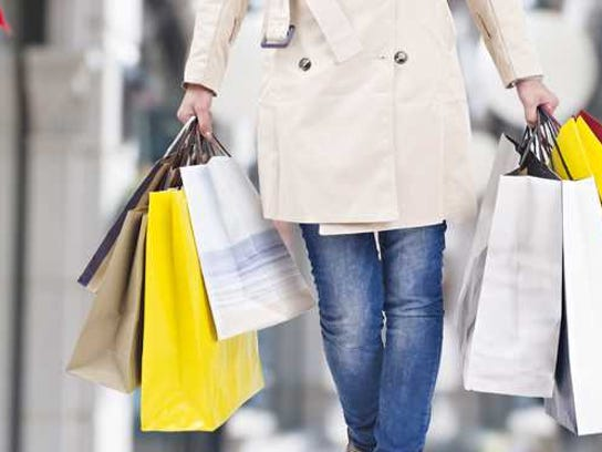 A woman carries several shopping bags.